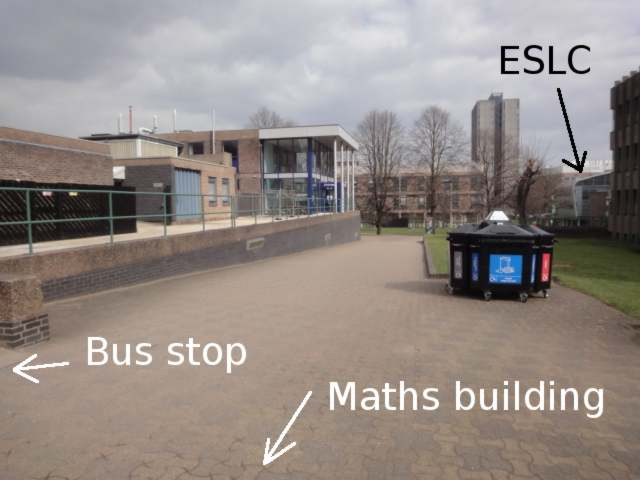 A path, paved in brick, which slopes down away from the viewer. Some recycling bins are nearby. At the bottom of the slope and to the right there is grass. Over to the right hand side of the photo, a building with a curved roof is labelled ESLC.