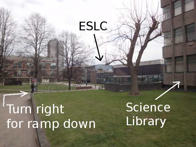 On the right is the corner of a light tan coloured building with rows of largish windows separated by vertical ridges, labelled Science Library. To the left of the picture is the edge of a path. In the distance a curved roof can be seen and is labelled ESLC.