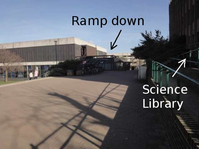 """A large paved area. On the left, the ground slopes down, and a couple of people are going down steps. On the right is the front of a large building, labelled Science Library. At the far end of the paved area, an arrow indicates """"Ramp down"""", although in this photo, the ramp itself can't be seen."""