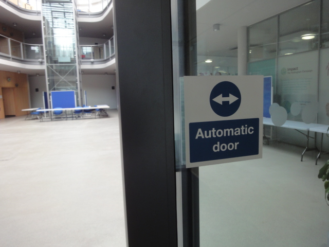 "Near to the camera is the edge of a door, with a sign saying ""Automatic door"". Beyond the door is a large atrium. Two balconies run round the edge of the atrium. A square glass column holds a lift."