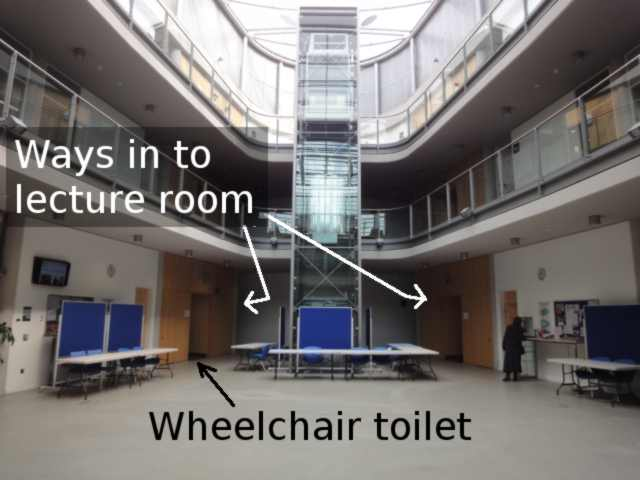 "Inside the Atrium. On the left, about level with the lift column, an archway is labelled ""Wheelchair toilet"". At the far end, routes lead off to left and right, marked ""Ways in to lecture room""."