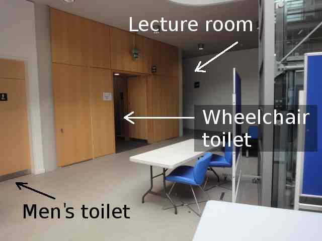 """Photo: In the foreground, to the right, is the vertical edge of a metal and glass column (for the lift). Ahead is the space to the left of the lift. Along the left hand wall, nearest is a light-coloured wooden door to the men's toilet. Next is an archway, with light-coloured wooden panelling all around. An arrow added to the photo indicates that this leads to """"Wheelchair toilet"""". At the back of the space is a corridor going off to the left. An arrow added to the photo labels this as """"Lecture room"""". A few blue office-type chairs and collapsible tables are near the lift column."""