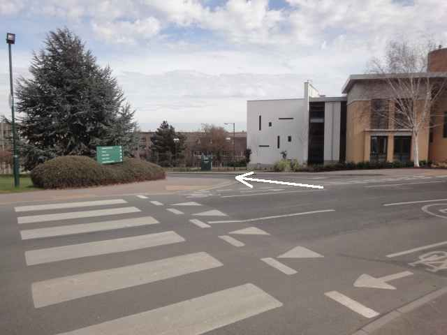 Photo: Across a road is a white and tan-coloured building. In front of the building is a turning off the main road. In the foreground of the picture is a zebra crossing across the main road.