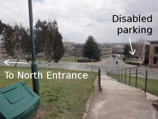 Photo: a view down steps, across a road, along another road. To the left of the far road, in the distance, is a building with vertical ridges (the Science library). To the right of the road, an arrow points towards a disabled parking area, although the parking space itself can't really be seen on the photo.