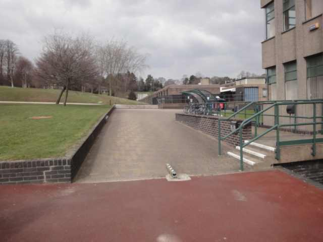 Photo: in the foreground is some reddish-brown tarmac. Ahead, the surface changes to brick or paving stones, sloping upwards. On the left is a low wall and some grass. On the right is the back of a building with vertical ridges. On the right, three steps lead up to the building (though this is not the main way in).