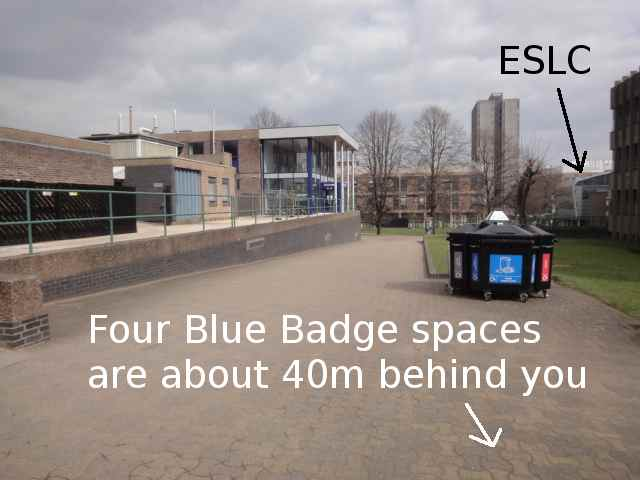 "A path, paved in brick, which slopes down away from the viewer. Some recycling bins are nearby. At the bottom of the slope and to the right there is grass. Over to the right hand side of the photo, a building with a curved roof is labelled ESLC. The foreground of the photo is annotated ""Four Blue Badge spaces are about 40m behind you""."