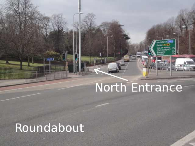 Photo: taken from the middle of a roundabout. Just ahead is part of the roundabout surface. Further ahead is a road into the distance. An arrow labels the North Entrance, a small exit left, just off the big main road as it leaves the roundabout.