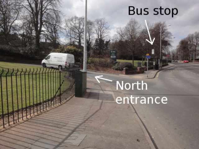 """Photo: Slightly to the right, a main road continues into the distance. In the centre of the photo, a smaller road leads to the left, labelled """"North entrance"""". On the pavement in the angle between the two roads is a bus stop with a shelter."""