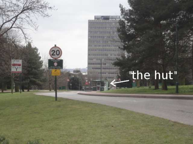 Photo: Ahead is a road leading to a small hut. The skyline is partly filled by a tall tower block behind the hut. A sign near to the viewer has a 20 speed limit. The right hand side of the road has a pavement; to the left of the road is grass.
