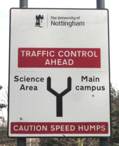 """Photo: a road sign. Against a red background are the words """"Traffic Control Ahead"""". A fork shape depicts two paths: the left labelled """"Science Area"""", the right """"Main campus"""". A second red box says """"Caution Speed Humps""""."""