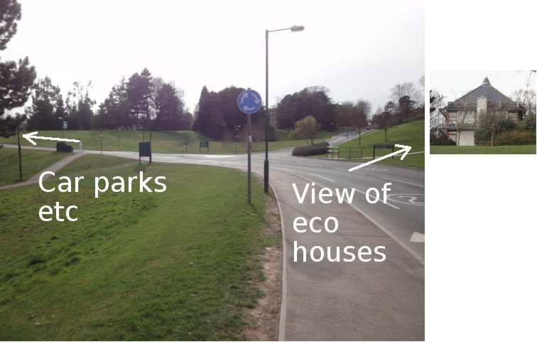 """Photo: Ahead is a small flat roundabout. To the left, the road is labelled """"Car parks etc"""". This road to the left is the first exit from the roundabout. To the right, the grassy hillside is labelled """"View of eco houses"""". Ahead, the roundabout's second exit leads into the distance, up a gentle slope. A small additional photo is of one of the eco houses (which are not shown in the main photo, only pointed to)."""
