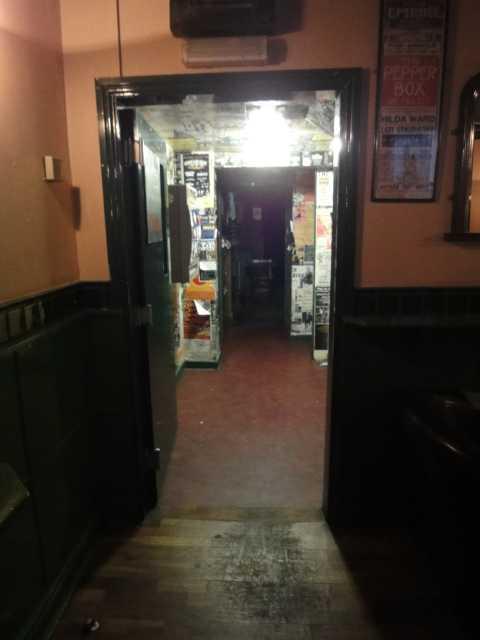 A doorway, with the door open, leads into a well-lit corridor. After perhaps 5 metres is another doorway.