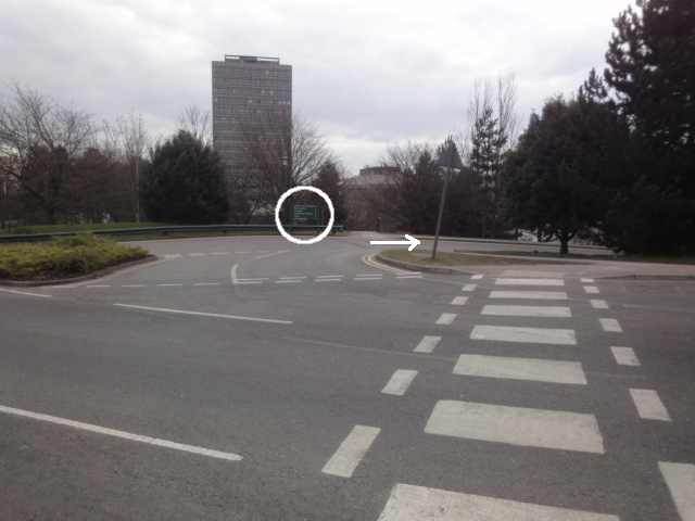 Photo: a junction. A main road runs across the foreground, with a zebra crossing across it. Just left of the zebra crossing, a very short section of road joins the first road with another one running parallel to it. A green sign on the far side of the second road is emphasised in the photo. The photo includes an arrow to the right from this sign along the further-away road. Against the skyline is a tall tower.