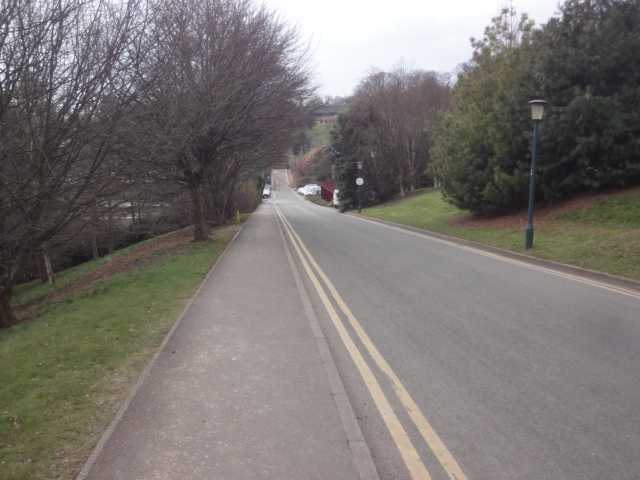 Photo: An empty road ahead slopes downwards. On both sides are grass and trees. On the left hand side is a pavement. In the distance can be seen a few parked cars. Just before the cars is the dark red edge of a building.