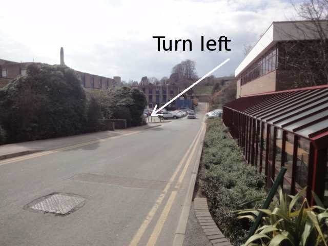 """Photo: In the foreground on the right is the front of a building, similar to a conservatory, with dark red window frames and roof slats. Ahead, a road slopes down past the buliding towards a car park and some other distant buildings. On the photo is a caption """"Turn left"""", pointing at a narrow turning left before the distant cars and buildings."""
