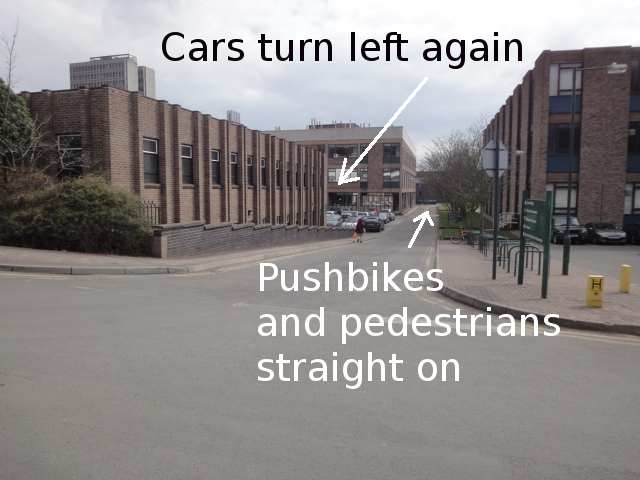 """Photo: In the foreground, a road runs from left to right. Ahead, another road runs towards buildings in the distance. A brick building on the left has double vertical ridges between its windows. The photo is annotated """"Cars turn left again"""" with an arrow just after that ridged building. It also says """"Pushbikes and pedestrians straight on"""", pointing towards the buildings in the distance."""
