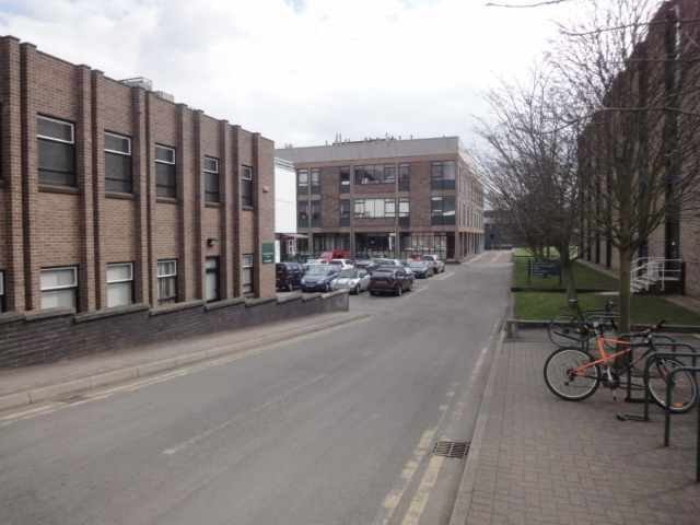 Photo: In the foreground is a road, with some bicycles parked on the pavement to the right. On the left is a brick building with double vertical ridges. Beyond the ridged building is a small car park, and a glimpse of a white-fronted building to the left of the car park. Another brick building is beyond the car park.
