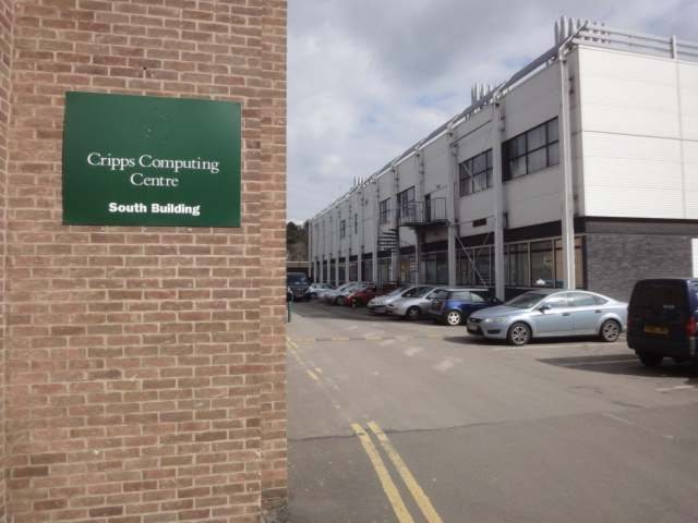 """Photo: In the foreground on the left is the corner of a brick building. On the building's wall is a green sign, """"Cripps Computing Centre, South Building"""". To the right of the building, a road leads away from the camera. It has a speed bump part way along. Some cars are parked on the right hand side, near a building whose upper section is white."""
