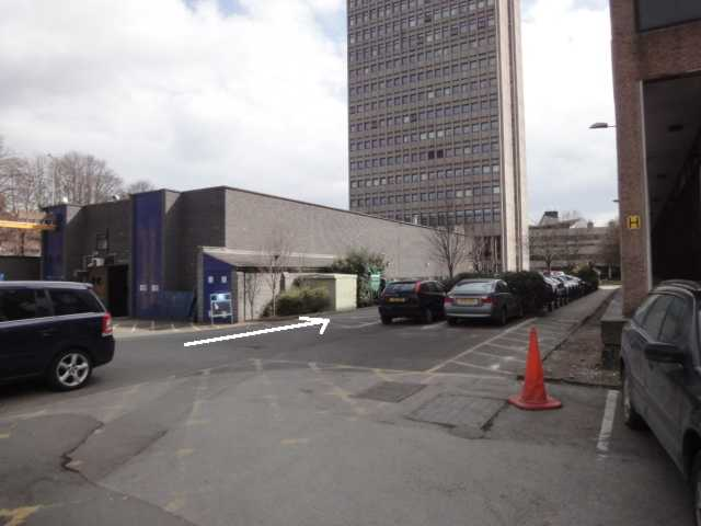 Photo: A short section of roadway leads towards a tall tower block against the skyline. Cars are parked along the right hand side of the road, in marked parking spaces. An arrow added to the photo points along the road. In the foreground to the right is the brown concrete corner of another building, and a little glimpse of a car parked in front of it. To the left of the road is a low building of dark grey brick, with some navy blue or dark purple doors on its end.