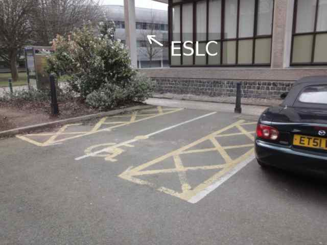 """Photo: Yellow lines on the road show the shape of a parking space, with a wheelchair sign in the middle. On either side of the parking space are yellow criss-cross hatchings showing spaces where no-one ought to park. The left hand side of the parking space is also the end of the road, after which is a flowerbed with a bush in it. Along the side of the road and the end of the parking space is a pathway. Beyond the pathway is a building. To the left of that building can be seen another. The second building is captioned on the photo """"ESLC""""."""