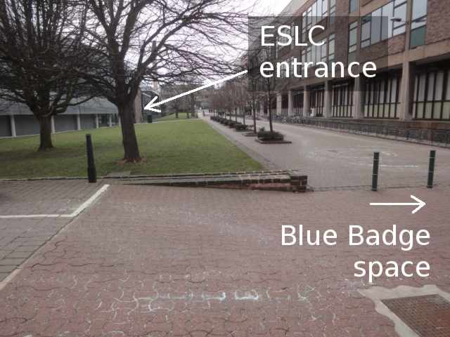 """Photo: A path runs into the distance. The photo is labelled with an arrow to the right indicating """"Blue Badge Space"""", although the parking space itself is off the side of the photo. To the left of the path is a grass lawn and a large grey building. To the right of the path is another building. At the far end of the grey building on the left, an arrow added to the photo indicates """"ESLC entrance""""."""