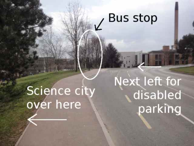 "Photo: A road leads towards a white and tan-coloured building. Ahead on the pavement to the left of the road, before the building, is a bus stop sign attached to a lamp-post. The photo has an arrow pointing left with the words ""Science City over here"". Further ahead, the photo has an arrow pointing left, and the words ""Next left for disabled parking""."