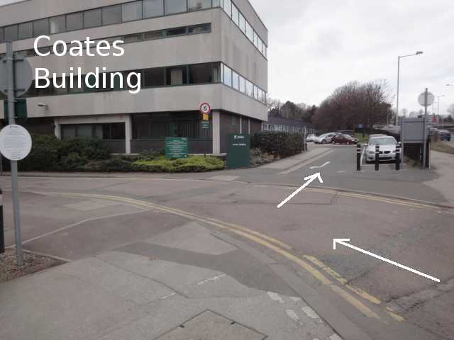 Photo: A road sweeps round towards the left, in front of a building. The building is mainly of grey concrete with rows of windows; its lowest storey is of dark brick. In front of it is a green sign with its name, Coates Building (although this is too far away to be read in the photo, and instead the photo has a label added with the name). To the right of the building, a small side-road leads round towards the back of the building. Arrows added to the photo indicate travelling up this side-road.