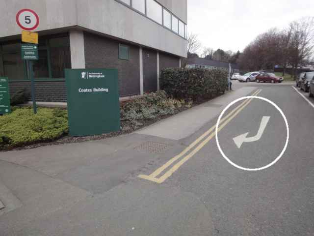 Photo: On the left is a building, and in front of it, a green sign shows its name, Coates Building. Ahead, to the right of the building, is a small road. On the road, a road sign arrow indicates a right turn, towards and to the left of the camera. That is, cars coming out of the road are being told to turn to the photographer's left. The photo has a circle added around this arrow on the road.