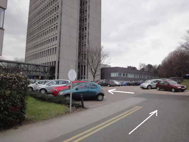 Photo: A small section of road leads to the right. The photo has an arrow added, pointing along the road. The road joins up with a car park to the left. A second arrow indicates crossing the car park to the left, towards an enclosed footbridge over the left-hand side of the car park. This footbridge connects two buildings. The right-hand building is visible in the photo and is a tall tower block.