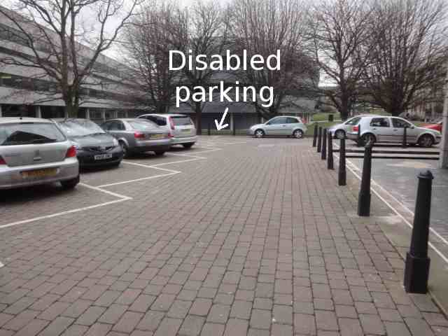 "Photo: On the left is a row of cars, arranged in parking spaces outlined in paint on the brick-paved ground. Ahead is a brick surface for driving forward on. At the far end of the row of cars, on the left, is a space. The photo has the added words ""Disabled parking"" with an arrow to this space. On the right, extending ahead, a row of iron posts prevent cars from going too close to a building. The corner of the building can just be seen. Another building is ahead, behind some trees."