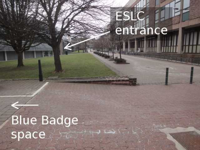 "Photo: A path runs into the distance. The photo is labelled with an arrow to the left indicating ""Blue Badge Space"", although the parking space itself is off the side of the photo. To the left of the path is a grass lawn and a large grey building. To the right of the path is a brick and concrete building. At the far end of the grey building on the left, an arrow added to the photo indicates ""ESLC entrance""."