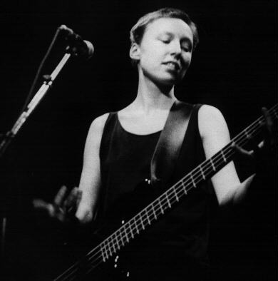 Photo: a younger Jennifer, playing bass at a gig.